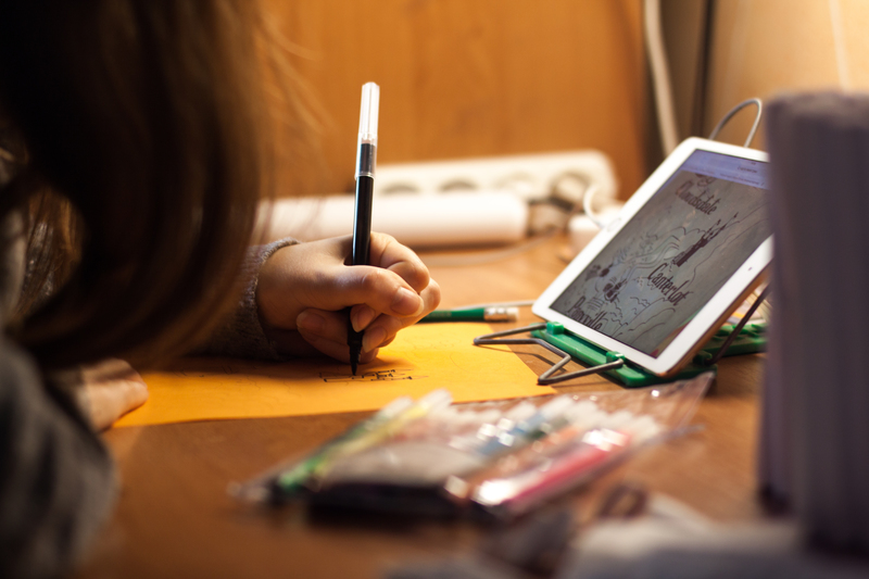 Student using a tablet computer and drawing